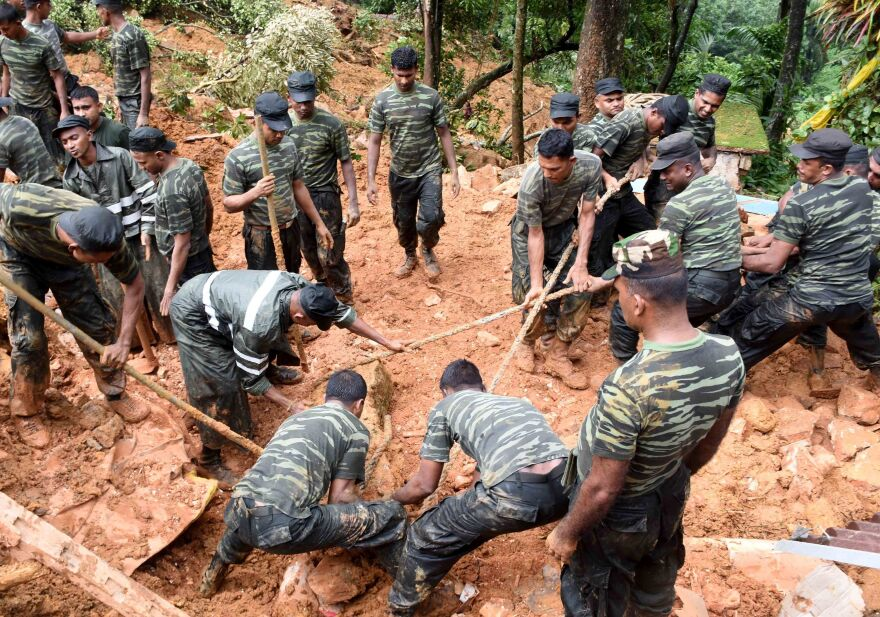 Sri Lankan military personnel work on rescue operations in the village of Bulathkohupitiya on Wednesday. Three days of torrential rain led to landslides in central Sri Lanka.