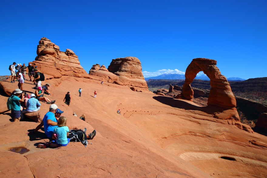 photo of tourists at delicate arch.