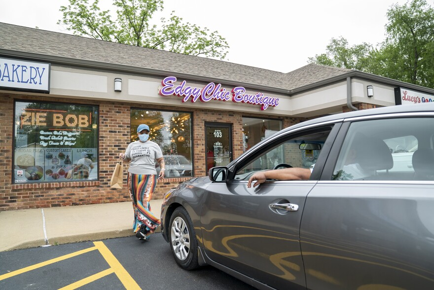 Angela Harris delivers a curbside order at her store, EdgyChic Boutique, in Fairview Heights on May 20. She's had many customers come to both her locations wanting to shop in person.  05 20 2020
