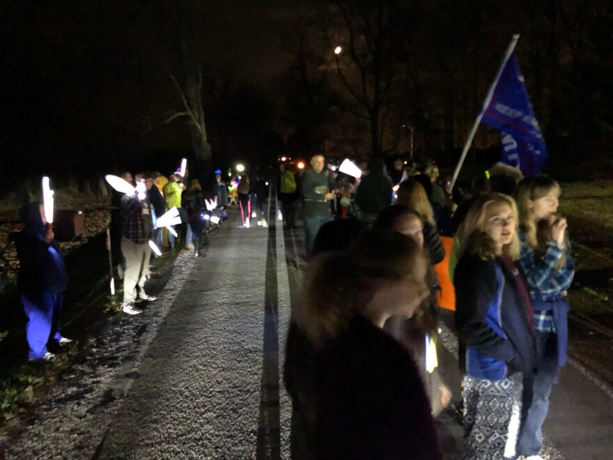 Protestors gather with flags and light-sticks on the road outside of Gov. DeWine's home
