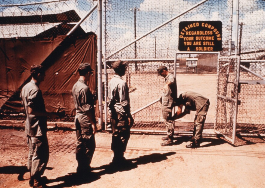 Guard searches prisoners at the gate to the pre-trial compound.