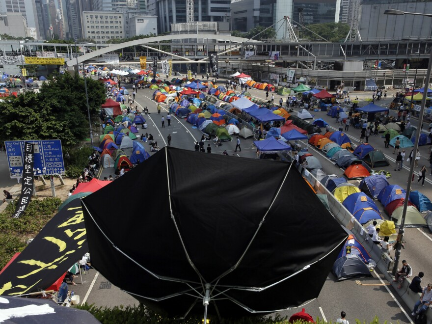 An umbrellas is placed near tents set up by pro-democracy protesters in an occupied area near government headquarters in Hong Kong on Thursday. Hong Kong officials have revived an offer for talks with the activists, but also emphasized that Beijing will never agreed to their demand for open elections.