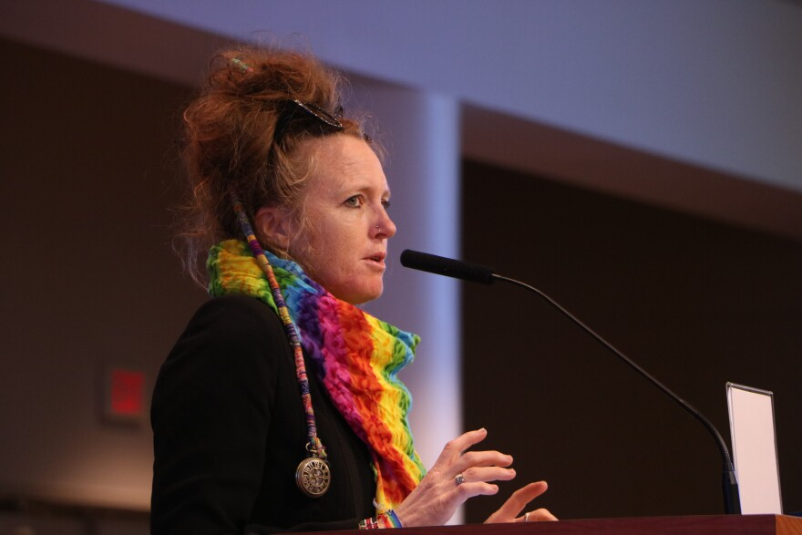 Person with red hair, sunglasses, and a rainbow scarf speaks into a mic at the podium.