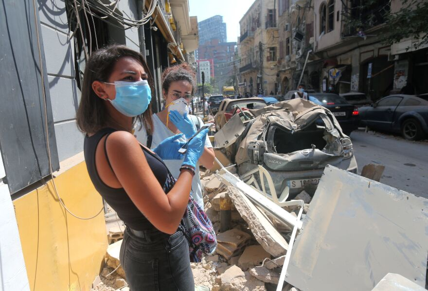 Women wearing face masks and gloves stand amid the rubble in Beirut's Gimmayzeh commercial district on Wednesday. The area was heavily damaged by the previous day's powerful explosion.