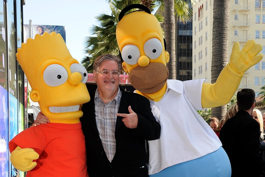 <em>The Simpsons</em> creator and cartoonist Matt Groening stands with Bart and Homer Simpson when they were honored with a star on the Hollywood Walk of Fame in 2012.