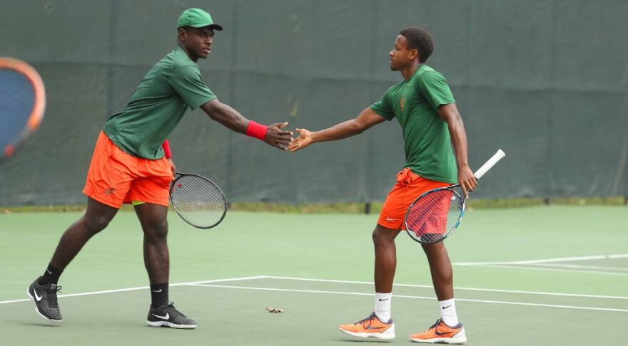 Two men in orange and green uniforms shake hands on a tennis field.