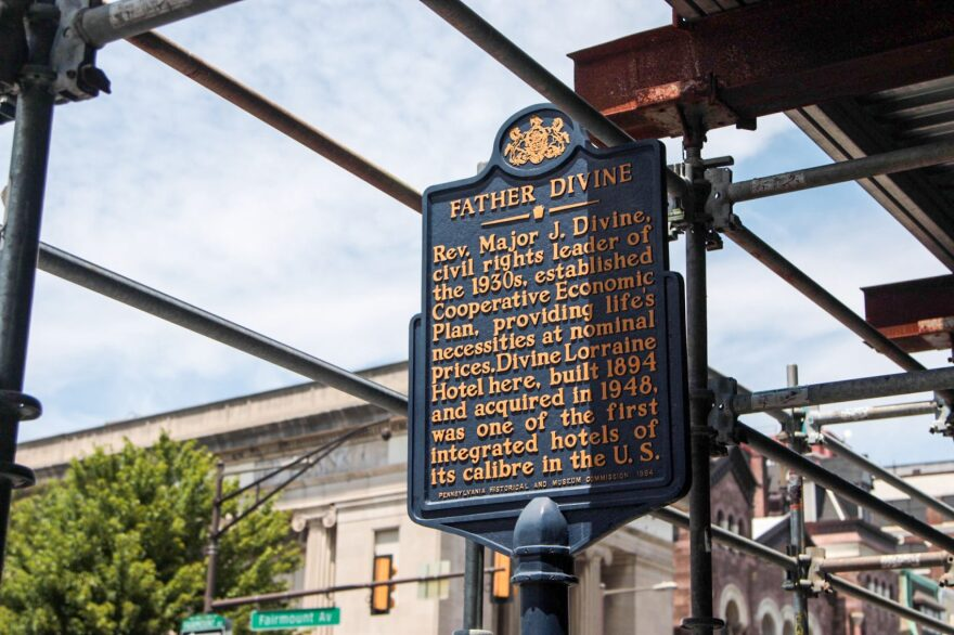 Outside of the Divine Lorraine Hotel, sign is posted about Father Divine, a spiritual leader and former owner of the hotel. (Dean Russell/Here & Now)