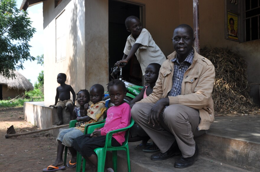 In Uganda's northern Amuru District, farmer Michael Okello sits outside his home with his younger children.