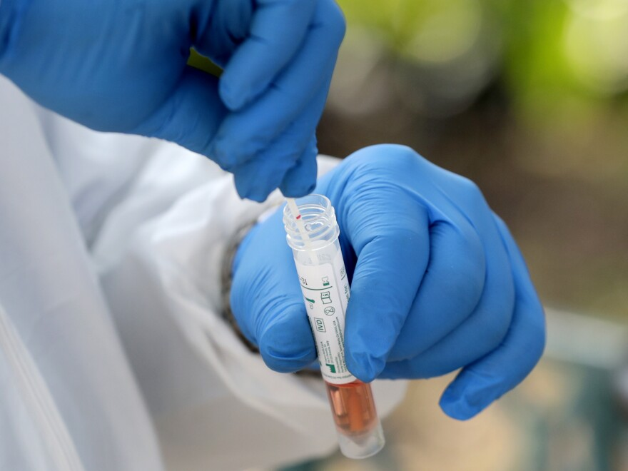 A medical worker places a swab in a vial while testing for the coronavirus through the Miami-Dade County Homeless Trust in Miami.