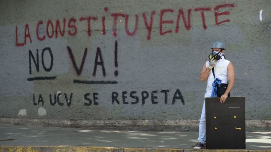 During a protest in Caracas this week, an opposition activist stands near graffiti against a proposal by Venezuelan President Nicolas Maduro to rewrite the constitution. A political and economic crisis has spawned often violent demonstrations by protesters demanding Maduro's resignation.