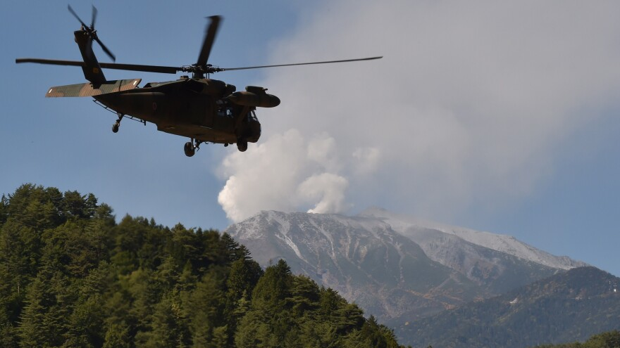 A military helicopter leaves a temporary landing site for a rescue mission on Mt. Ontake in Nagano prefecture Monday. Rescue efforts had to be suspended Monday, as the volcano vented toxic gases.
