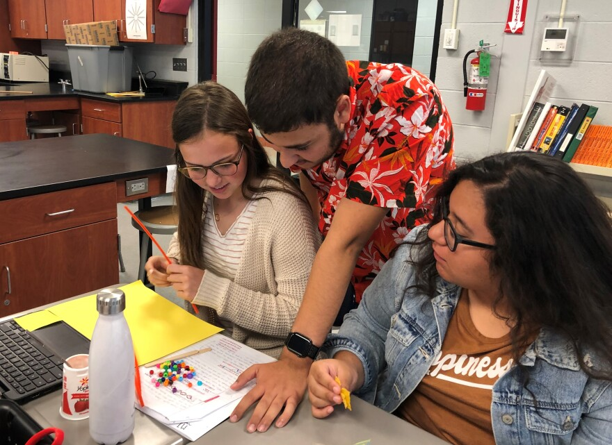 Keith Alyan, center, tutors students in an advanced science class. Alyan is doing A+ even though he wants to go to the University of Kansas, which doesn't honor the Missouri scholarship.