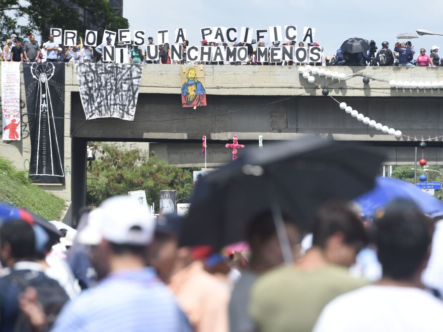 Protesters display signs from an overpass Monday in Caracas as they call for Maduro's ouster. The president blames the unrest — and the economic troubles that helped inspire it — on foreign powers like the U.S.