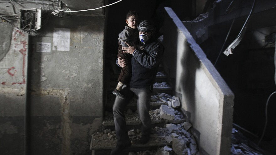 A man wearing a mask holds a child rescued at a site hit by what activists said were barrel bombs dropped by government forces in the northern city of Aleppo on Friday.