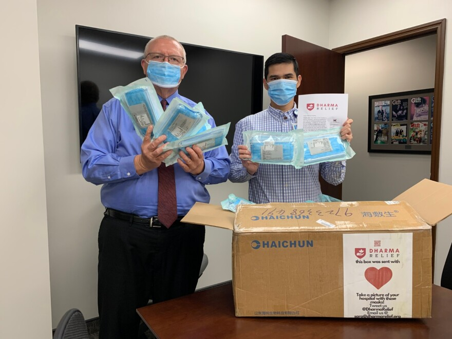 Workers from the Lee Health Foundation in Fort Myers, Florida hold up surgical masks sent by Dharma Relief.