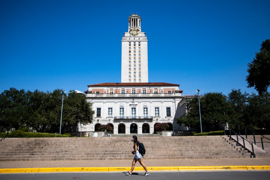 A student wearing a face mask walks past the UT tower.