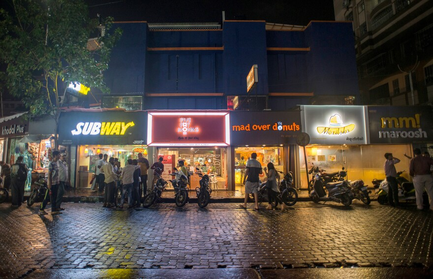 Pedestrians visit fast-food restaurants in Mumbai, India. Rapid urbanization in many developing countries is driving the demand for fast foods and highly processed, packaged foods.