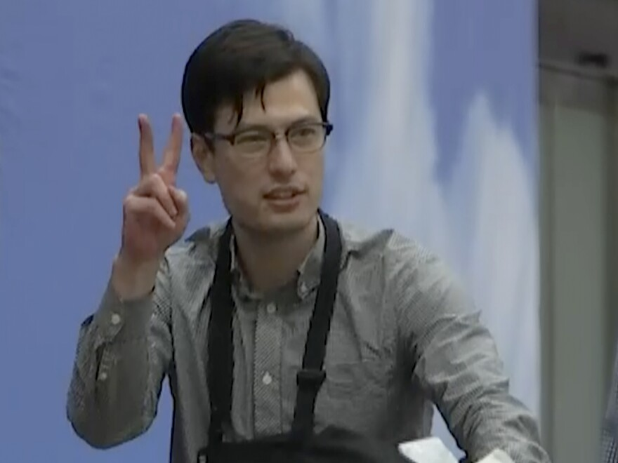 Australian student Alek Sigley gestures as he arrives at the airport in Beijing on Thursday. The 29-year-old vanished in Pyongyang more than a week ago.