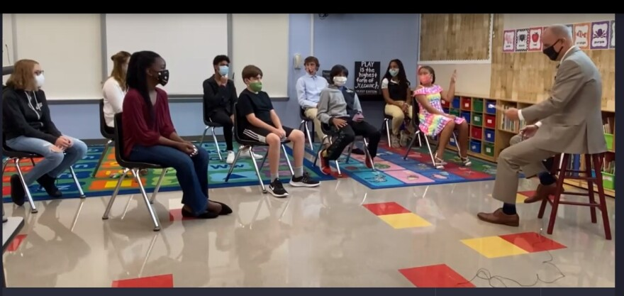 Man on stool speaks to students in classroom. All are wearing surgical masks.