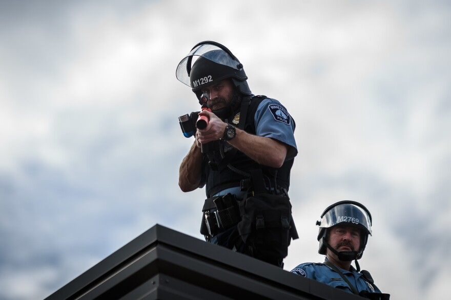 A police officer holds a projectile launcher during a demonstration in a call for justice for George Floyd following his death.