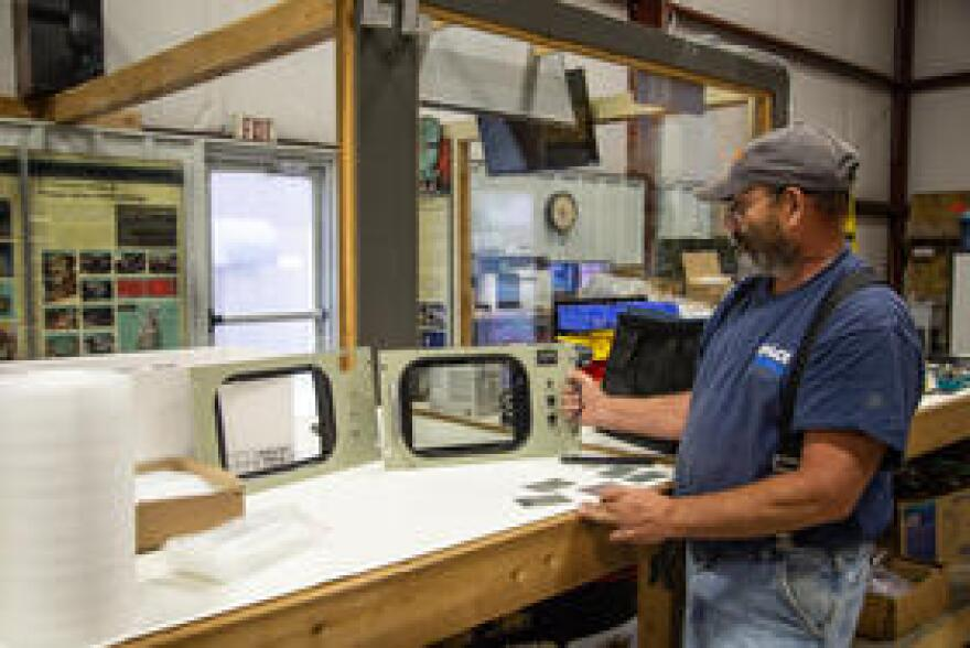Technician Don Aich shows how an upgraded monitor plate looks identical to an original.