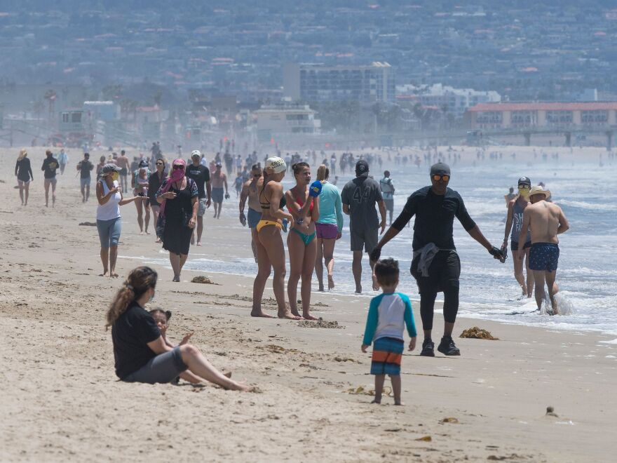 Californians enjoy the Manhattan and Hermosa beaches on Wednesday, the first day that Los Angeles County allowed beaches to reopen after a six-week closure during the coronavirus pandemic.