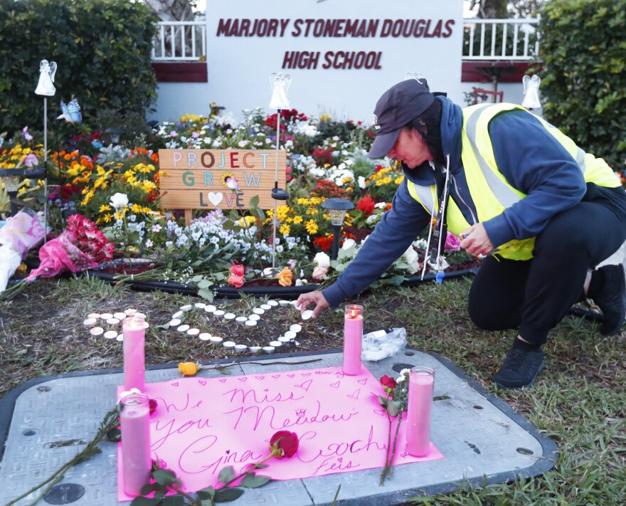 School crossing guard Wendy Behrend lights a candle at a memorial outside Marjory Stoneman Douglas High School during the one-year anniversary of the school shooting, Thursday, Feb. 14, 2019, in Parkland, Fla. A year ago on Thursday, 14 students and three staff members were killed when a gunman opened fire at the high school.