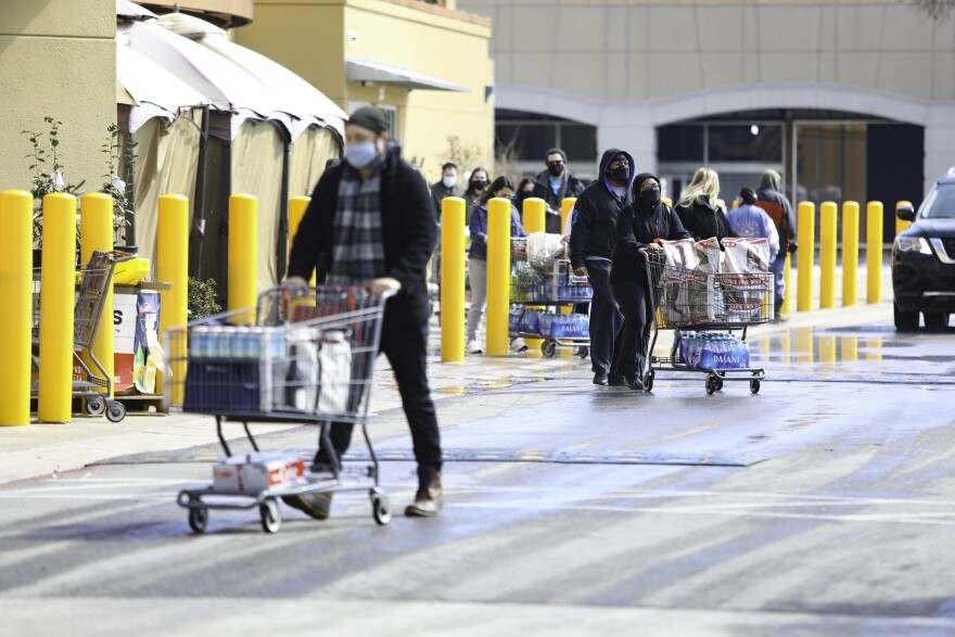 Shoppers leave the H-E-B at the Hancock Center on Friday with carts full of water and other goods.