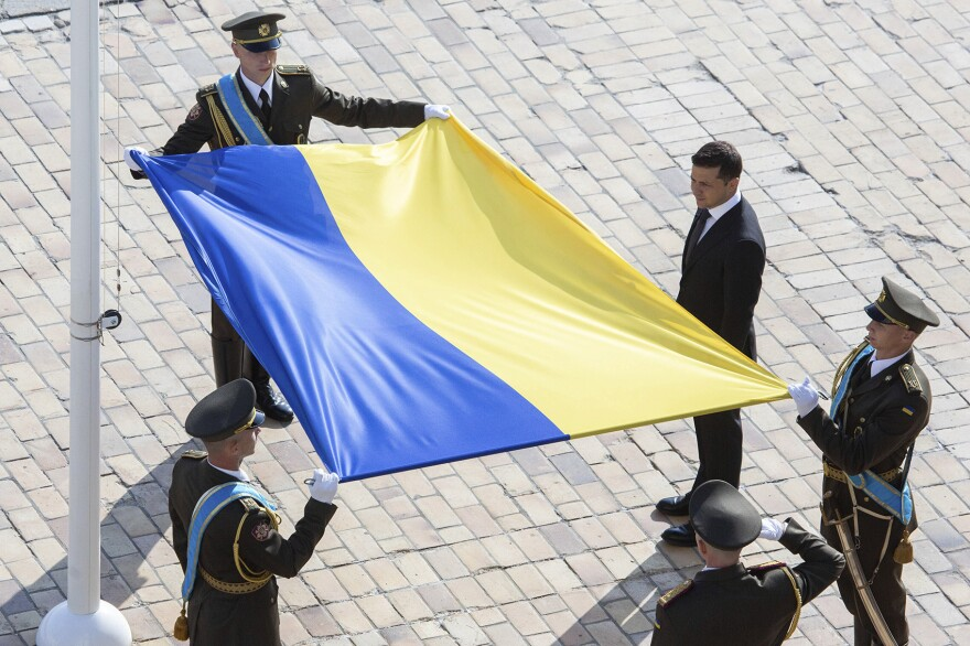 Ukrainian President Volodymyr Zelenskiy, right, attends a ceremony during the National Flag Day celebration at the St. Sophia square in downtown Kyiv, Ukraine, Friday, Aug. 23, 2019. (Ukrainian Presidential Press Office via AP)