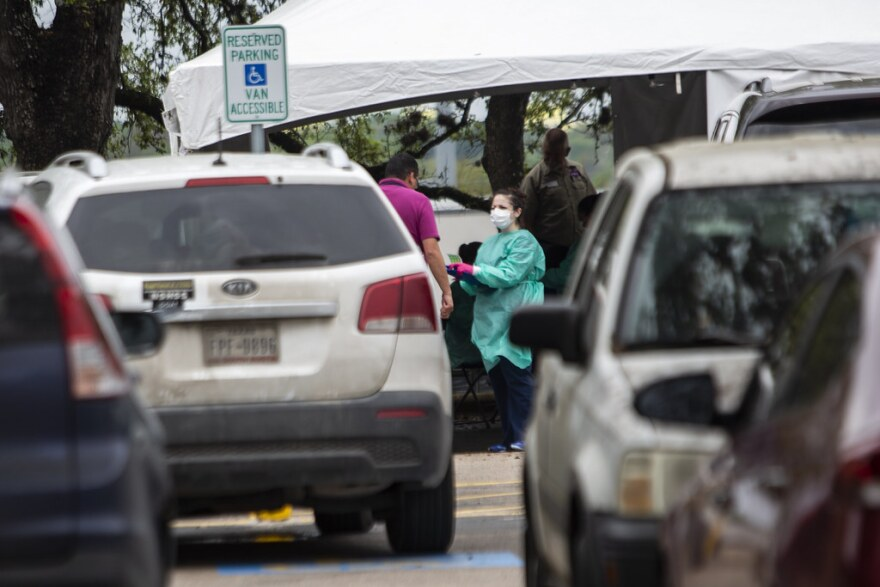 A woman in a mask and scrubs talks to someone at a drive-thru coronavirus testing site in South Austin.