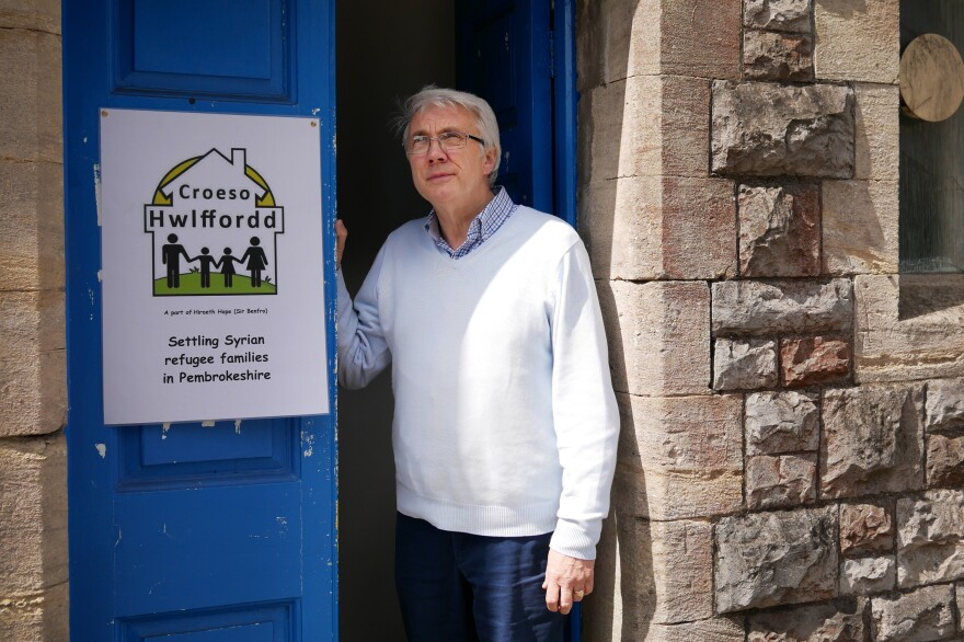 Jeff Britten stands in the doorway of the Baptist chapel where he meets regularly with other members of his group sponsoring a refugee family. The name of the group is Croeso Hwlffordd, or Welcome Haverfordwest.