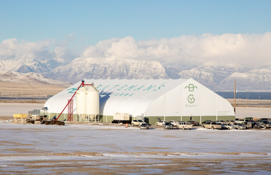 A large white hanger-like structure sits on a snowy field. Snow capped mountains are visible in the background.