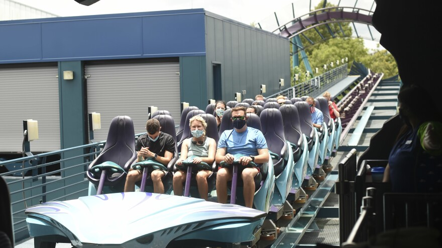 Visitors wear face masks while riding a roller coaster Thursday at the SeaWorld amusement park in Orlando, Fla. SeaWorld is reopening this week after being closed due to the COVID-19 pandemic. Florida and more than 20 other states continue to see a rise in new daily cases.