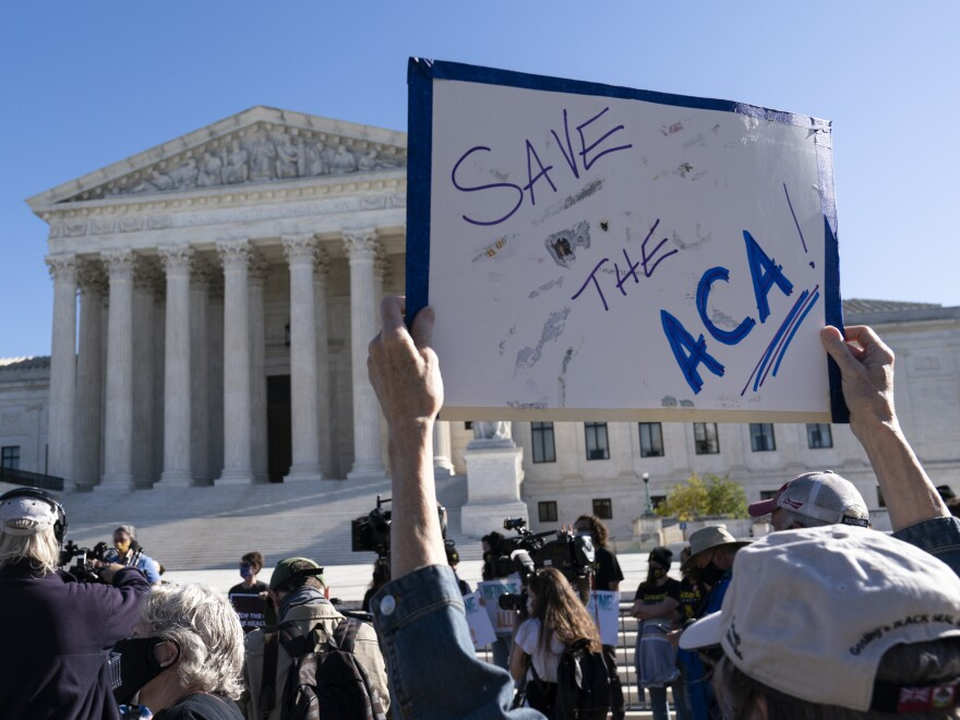 A demonstrator holds a sign in front of the U.S. Supreme Court, which heard arguments Tuesday on the future of the Affordable Care Act.
