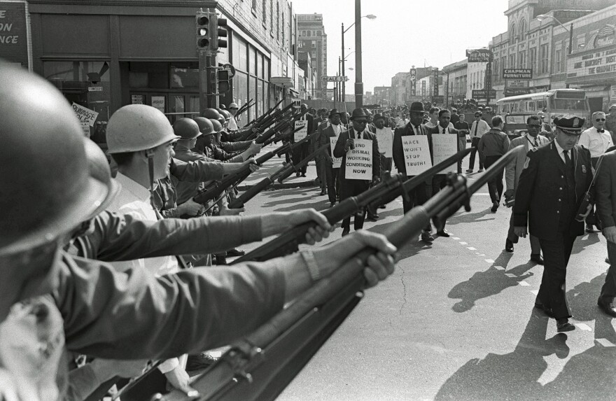In February of 1968 Black sanitation workers of Memphis  began a strike to demand better working conditions and higher pay. In this March 29, 1968, photo, striking workers march past Tennessee National Guard troops with fixed bayonets during a 20-block march to City Hall in Memphis, Tenn.