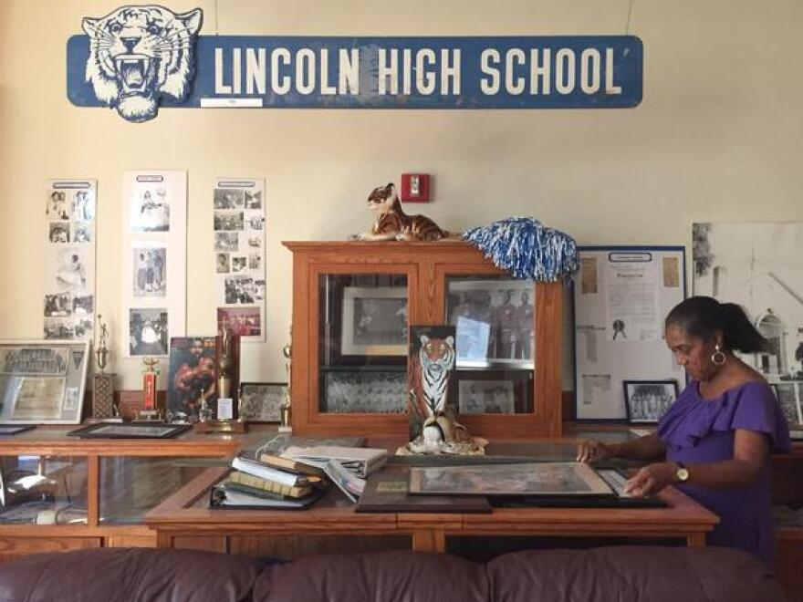 Former Lincoln High student and teacher Althemese Barnes looks through old photos of the school.