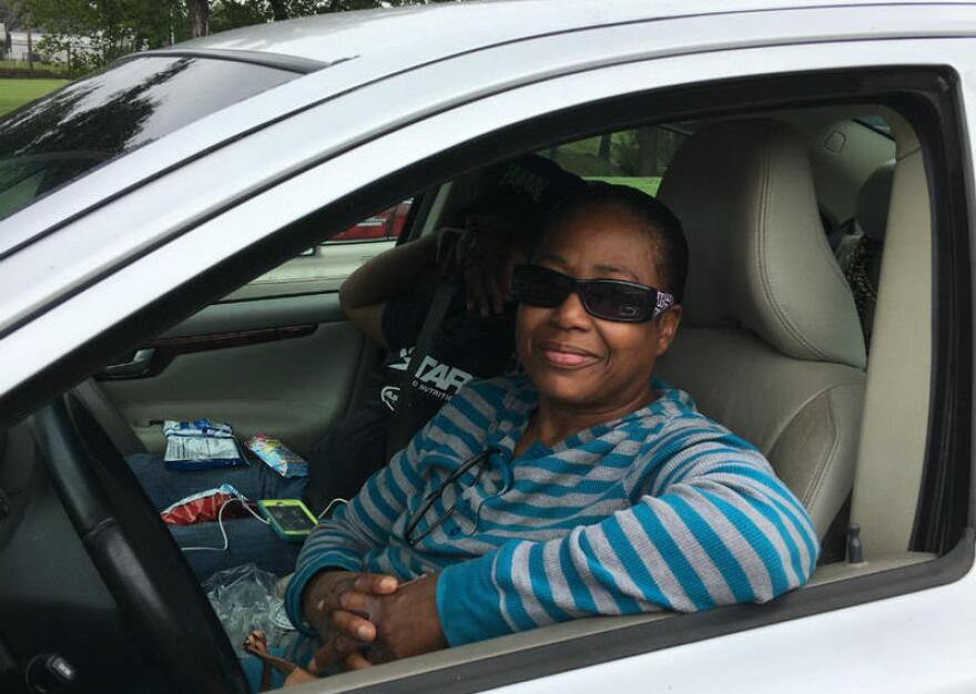 Lorrine Adamore in her car with son Julian. They've lived 12 years in Houston, after leaving New Orleans, by boat, during floods of Katrina. (Bill Zeeble/KERA News)