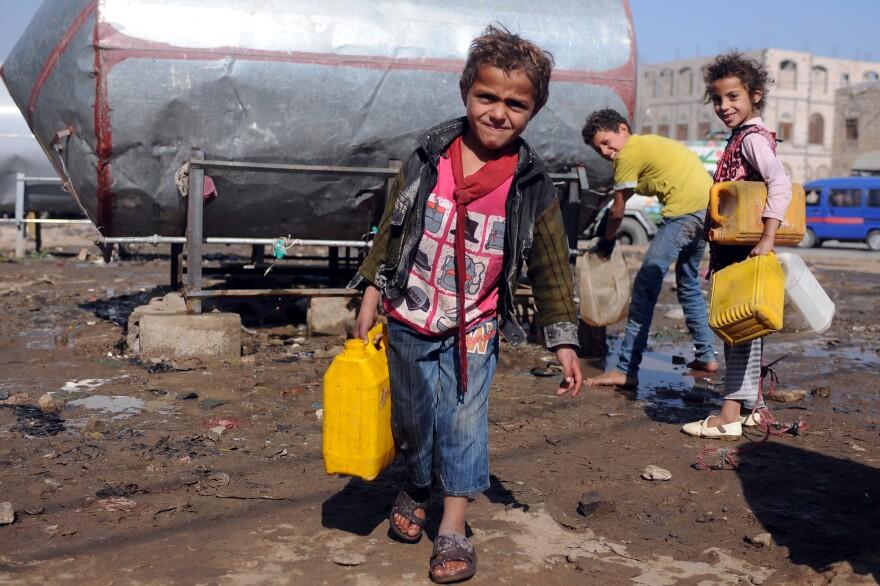 Yemeni children fill jerrycans with clean water in Sanaa, Yemen.