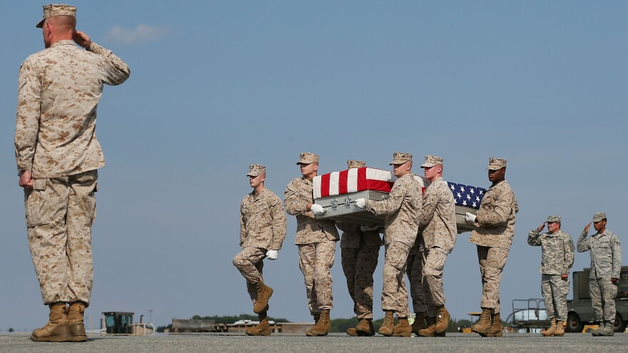 """Aug. 13: At Dover Air Force Base in Delaware, the remains of Marine Lance Cpl. Gregory T. Buckley are carried during a dignified transfer. He was killed in a """"green on blue"""" attack."""