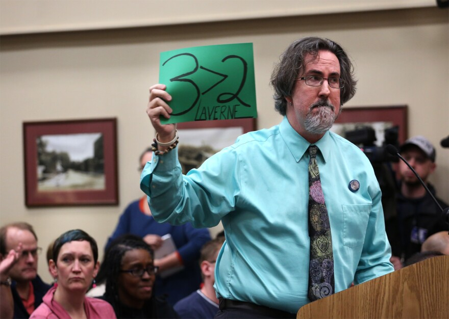 Ferguson resident John Powell holds up a sign referencing a recent vote in which three city council members voted for Laverne Mitchum to fill Brian Fletcher's council seat on Feb. 2, 2016.