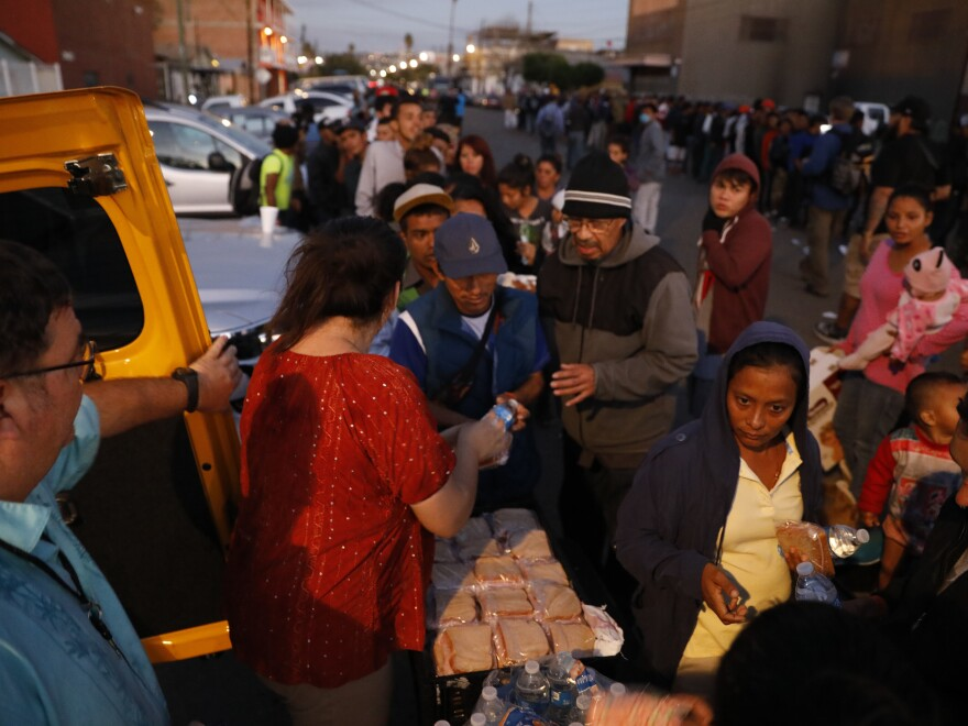 Well-wishers distribute food to migrants outside of a sports complex where more than 5,000 Central Americans are sheltering, in Tijuana, Mexico. President Trump wants the migrants to stay in Mexico while their asylum claims play out in U.S. immigration court.
