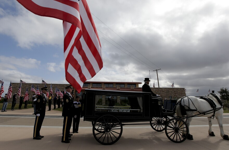 An honor guard places the remains of Army Sgt. Charles Schroeter in the back of a a horse-drawn hearse.
