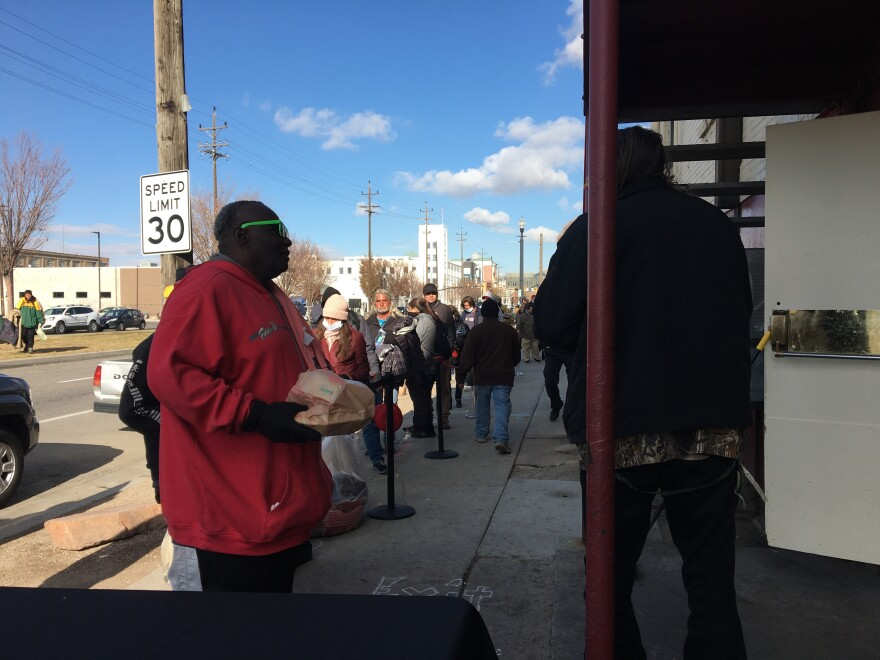A photo of a line of homeless people waiting to get food.