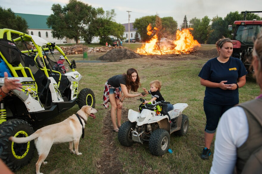Bailey Morris and her nephew Tucker Lynn play with a dog at a bonfire during Old Settlers Days in Alexander in September. The coals of the bonfire are used to cook about 1,000 pounds of meat to feed celebrants during the annual festival.