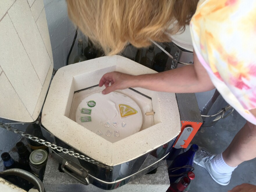 Michele Palenik lowers the pendants into her kiln to fuse the glass plates together and seal in the cremated remains.