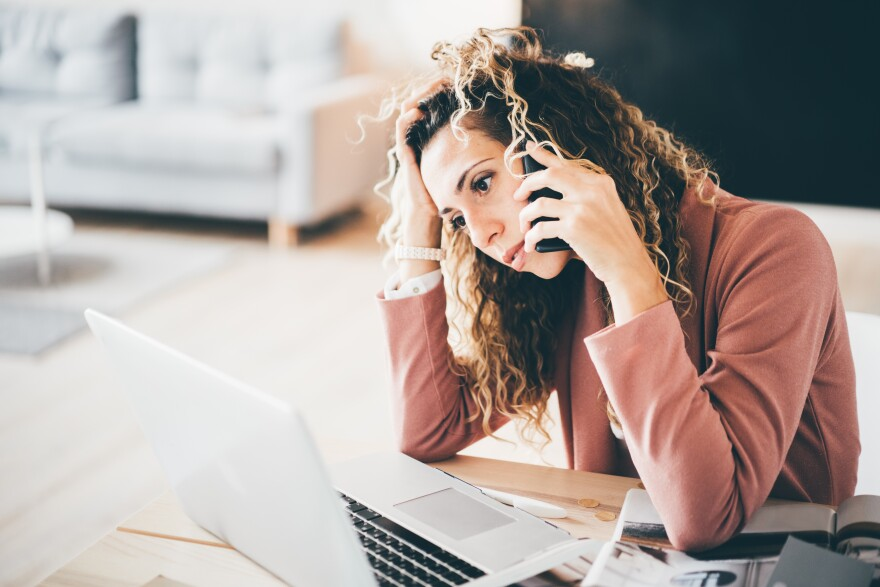 Busy woman suffering stress working at laptop while talking on mobile phone.