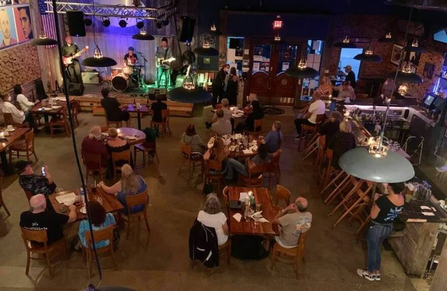 An overhead look at restaurant/club with people at tables and a music stage.