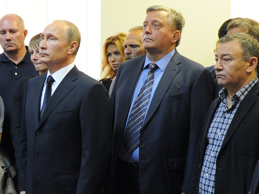 In Aug. 2013, Russian President Vladimir Putin (left) and businessman and billionaire Arkady Rotenberg,(right) mourn during a farewell ceremony for Putin's first judo coach, Anatoly Rakhlin, in St. Petersburg, Russia.