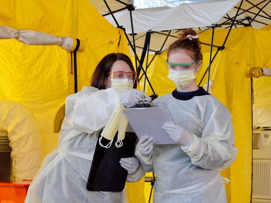 Hospital clinicians work on testing patients for the coronavirus at Newton-Wellesley Hospital in Newton, Mass., where the hospital has set up tents in a parking garage.