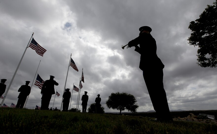 A rifle squad fires a salute at the conclusion of the ceremony as a bugler plays taps for Army Sgt. Charles Schroeter.